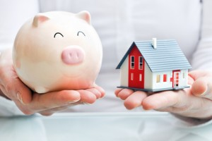 hands-holding-a-piggy-bank-and-a-house-model