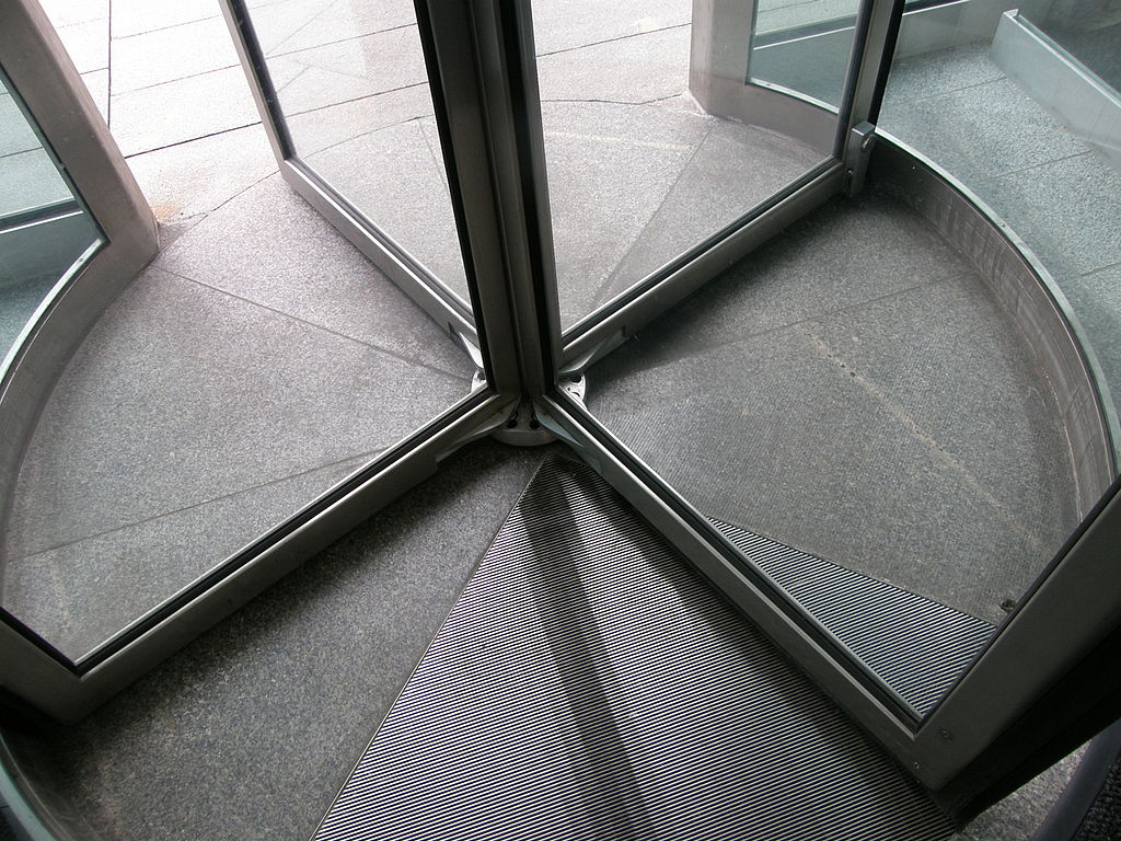 Why are revolving doors more energy-efficient than swing doors?